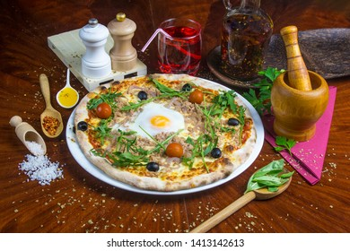 Bio pizza with tuna, egg, tomato, olive, salad. Presented with spicy oil and several decorative elements. Served on a round wooden table.