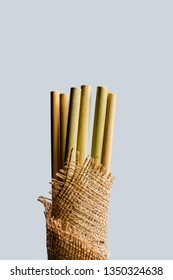 Biodegradable bamboo straws on a gray background. Eco straws made of bamboo. Packaging straws made of bamboo.