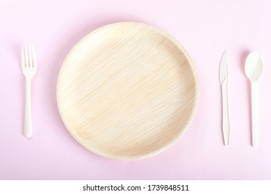 Biodegradable disposable plate, spoon, for and knife on light pink background
