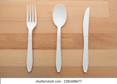 Biodegradable plastic spoon, fork and knife made from starch on wooden background