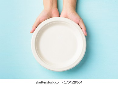 Biodegradable plate, Compostable plate or Eco friendly disposable plate holding by hand on pastel color background