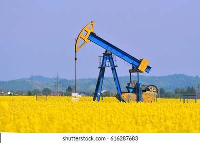 biodiesel concept (a pump jack with a canola field in background)