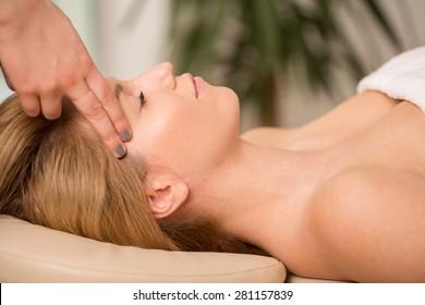 Bioenergy therapist healing young woman's headache