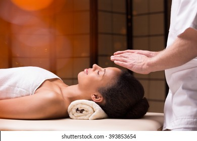 Bioenergy therapist holding his hands above young woman's head