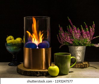Bioethanol fueled portable fireplace burning at home, for live fire at home, no chimney and mantelpiece is needed. Liquid  bio ethanol burns in cup. Black background, green tea cup, apples in bowl.