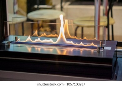 Biofireplace burn on ethanol gas. Contemporary mount biofuel on ethanol fireplot fireplace close-up. Modern smart ecological alternative technologies. Interior design of a house inside