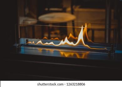 Biofireplace burn on ethanol gas. Contemporary mount biofuel on ethanol fireplot fireplace close-up. Modern smart ecological alternative technologies. Interior design of a house inside