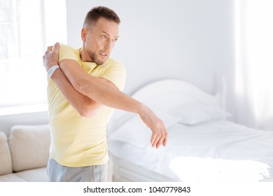Biohack flexibility. Pleasant sportive vigorous man stretching while turning aside and standing on light background