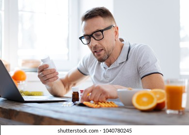 Biohack your life. Handsome progressive doubtful man deciding about biohacking supplements while sitting and improving his health
