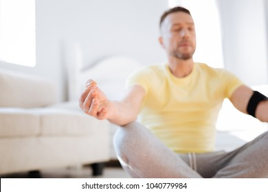 Biohacking discovery. Selective focus of male hand resting on knee while relaxing and practicing meditation