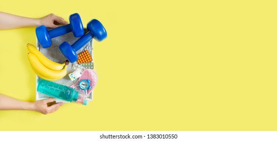Biohacking health treatment with the help of sports, healthy nutrition, sleep and vitamins. Woman's hands hold a tray with a set for biohacking on a yellow background flat view