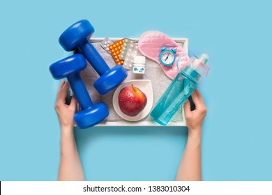Biohacking health treatment with sports, healthy nutrition, sleep and vitamins. Woman's hands hold a tray with a set for biohacking on a blue background flat view