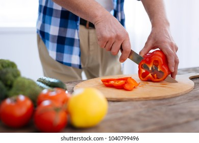 Biohacking ideas. Close up of male strong hands touching bell pepper while using knife and slicing it