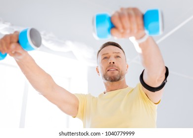 Biohacking instruments. Low angle of strong pensive determined man smiling while using dumbbells and working out