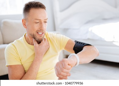 Biohacking tricks. Bearded cheerful skillful man touching neck while using fitness watch and looking down