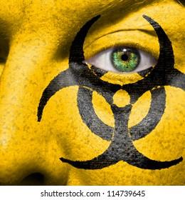Biohazard symbol painted on face with green eye to raise awareness for bio hazardous waste