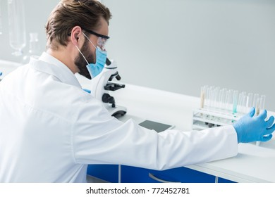 Biological innovations. Nice professional smart biologist wearing a mask and taking a test tube while conducting a professional research