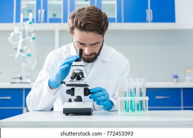 Biological research. Smart nice confident scientist looking into the microscope and testing the samples while doing the biological research
