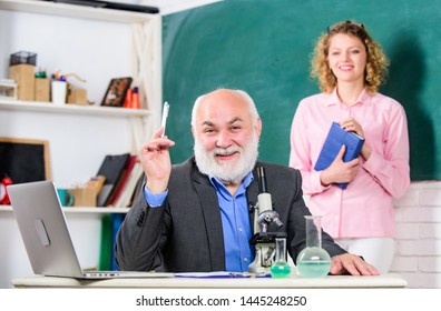 Biological research. Teacher and girl with notepad near chalkboard. College university education. Biologist or chemist with microscope teaching student biology. Biology science. Study biology.