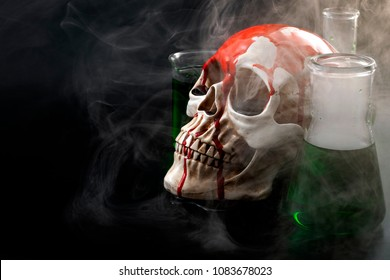 Biological warfare, chemical attack and genocide concept with a skull surrounded by chemistry flasks with smoke or mustard gas coming out of the green liquid with copy space