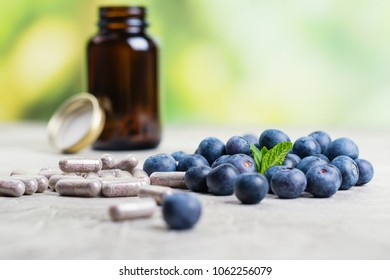 Biologically active supplement - pills for healthy eyes on green lushious background. Copy space