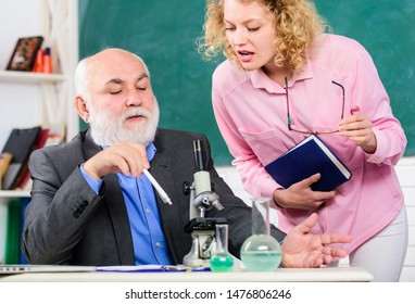 Biologist or chemist with microscope teaching student biology. Study biology. Biological research. College university education. Teacher and girl with notepad near chalkboard. Biology science.