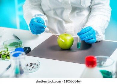 Biologist examining apple for pesticides