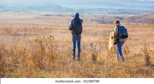 Biologists walking through the field at sunset nearby Stanca village, Iasi, Romania.