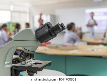 Biology or chemistry science class study with microscope and blur background of school student group learning in blurry lab classroom with teacher for education concept