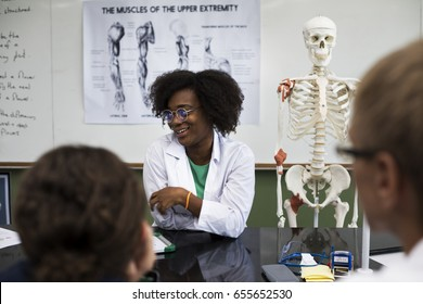 Biology teacher teaching biology to diverse group of high school students
