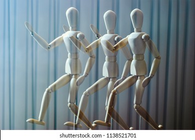 Biomechanics/People walking movement deconstruction using a wooden dummy and multiple exposures in bright light against a line pattern background.