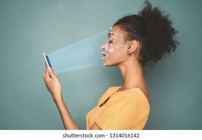 Biometric identification. African-american woman scanning face with facial recognition system on smartphone