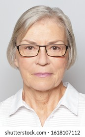 Biometric passport photo of a senior woman with glasses, neutral gray background.