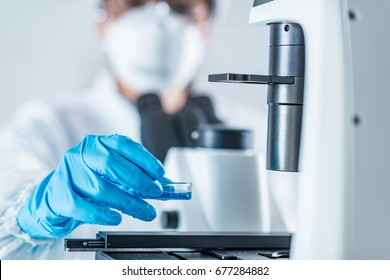 Biotech lab research, placing petri dish with cell culture under the microscope