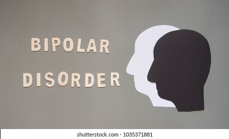 Bipolar disorder presented by double human head made from black and white paper on gray background w/ wood word. Manic and depress emotion. Mental health, brain disorder and psychological concept.