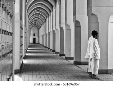 BIR ALI,MEDINA,SAUDI ARABIA-APRIL 22,2010: Black and white image of two Muslim men in ihram clothes look on at Bir Ali mosque in Al Madinah, Saudi Arabia.
