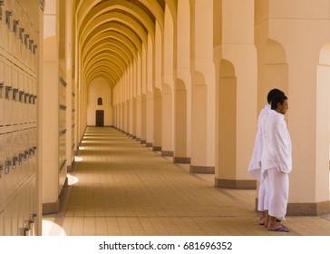BIR ALI,MEDINA,SAUDI ARABIA-APRIL 22,2010: Two Muslim men in ihram clothes look on at Bir Ali mosque in Al Madinah, Saudi Arabia.