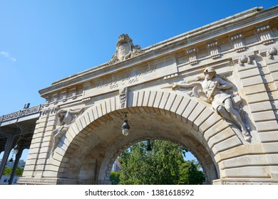 Bir Hakeim bridge arch with statues in a sunny summer day in Paris, France