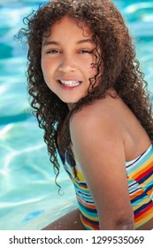 Biracial African American happy smiling young girl child relaxing on the side of a swimming pool