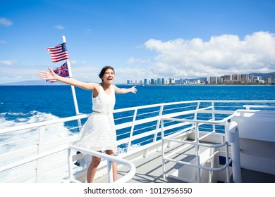 Biracial Asian, Caucasian teen girl standing on deck of cruise ship sailing in Waikiki bay,  arms outstretched in the wind. Honolulu Waikiki highrise hotels in background.