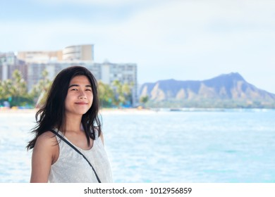 Biracial Asian, Caucasian teen girl standing in Waikiki by the ocean, smiling. Diamond Head Crater and high rise buildings in background.