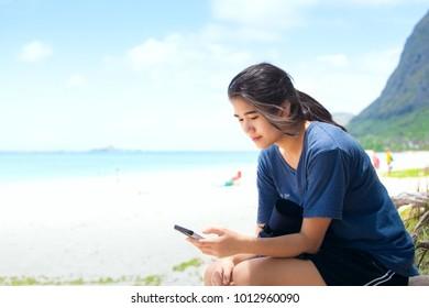 Biracial Asian, Caucasian teen girl sitting on sunny beach in Hawaii looking at smartphone