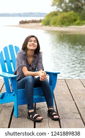 Biracial Asian Caucasian teen girl sitting on blue adirondack chair outdoors by lake, smiling