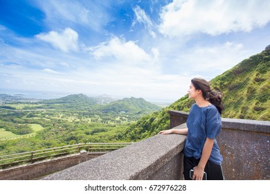 Biracial Asian Caucasian teen girl standing looking out over valley and hills of eastern Oahu, Hawaii