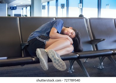 Biracial Asian Caucasian teenage girl sleeping on airport bench, tired