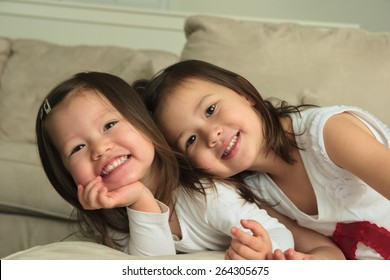 Biracial asian toddler sisters laying on stomach smiling at camera