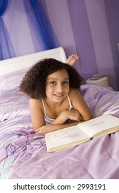Biracial beauty on her bed reading