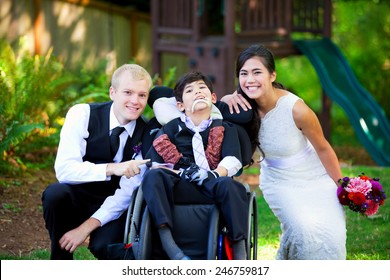 Biracial bride and groom with her little disabled brother in wheelchair on their wedding day
