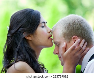 Biracial bride kissing Caucasian groom on forehead. Diverse couple