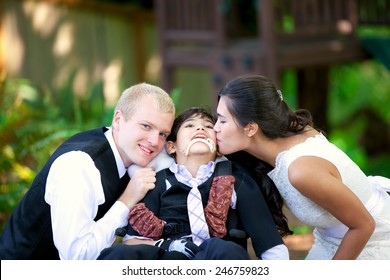 Biracial bride kissing her little brother on her wedding day. Child is disabled, in wheelchair